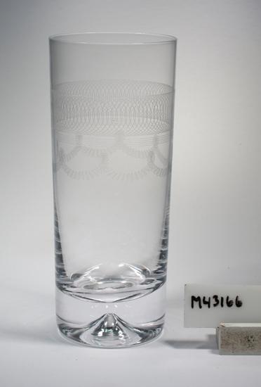 """Grogglas """"Capri"""". Art.nr. 4-118-39-S. Slät. Konstnär: Folke Walwing. Beskrivning: Närmast cylindriskt smal. Trattformad grop i den extratjocka botten. Bred bård av spiraler. Fyrdubbel, vågrät linje. Girlanger av femdubbla, småvågiga linjer. Färg: Ofärgat klarglas. Teknik: Blåst, sprängt, pantograferat. Mått: Diameter ovan avser glasets övre diameter. Bottendiameter: 58 mm. Rymd: 39 cl. Märkning: Klisterremsa med text. Se """"Signering, märkning"""" ovan. Inskrivet i huvudkatalogen tidigast 1985.  Kataloger: Form; se kataloger efter 1965 (Flygsforsgruppen).  Se även M 43167 - M 43169, samma dekor. Funktion: Grogglas"""