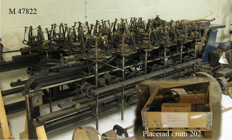 """Pantograf. Pantografen är tillverkad i Tyskland någon gång på 1930-talet. Denna användes på Åfors glasbruk fram till ca 1960. P.g.a. det omfattande arbete detta innebar, var inte denna form av etsning lönsam allteftersom modernare tekniker tog över denna del av etsning.   Pantografen i sig består av 3 enheter. En s.k. styrenhet plus två pantografdelaar där ritstiften är placerade. Själva styrenheten består av en järnställning där styrstiftet är fästad vid en styrarm som i sin tur är fästad vid ett länksystem som är röligt i sidled framåt/bakåt. Detta är vilande på ett hjulsystem, vilket möjliggör rörligheten. På vardera sidan om styrenheten står de bägge pantograferna, vilka var och en kan """"laddas"""" med 24 glas för stiftritning. Denna pantograf sköttes ensam av en gravör vid namn Albert Johansson.   Själva tillvägagångssättet för användandet av pantografen tillgår på följande sätt: Glasen doppas i ett vaxbad,  därefter ställdes de upp på pantografens 24 s.k. karuseller, vilka är höj- och sänkbara, där man placerade en tyngd på samtliga glas för att dessa skulle stå stadigare. Därefter placerar sig gravören vid styrenheten där ett träbord med en mässing/stålplatta med den önskade gravyren finns, gravören för sedan stiftet, som är fästad i styrarmen, längsmed gravyrspåren i mässing/stålplattan, samtidigt som han med foten trycker ner en bred fotpedal, varvid de fem stiften, som är placerade runt om varje glas, ritar sig in genom vaxet och återger samma mönster som finns på mässing/stålplattan. Kan tilläggas att gravören hade en tyngd på foten p.g.a. den kraft som krävdes för att trampa ner pedalen.  Efter stiftritningen togs glasen bort från karusellerna, och placerades på ett underlag där man vaxade fast dem på underlaget, för att sedan sänkas ned i ett syrabad, där syran frätte sig in i glaset, varvid det önskade mönstret uppstod. När detta var gjort, sänktes glasen ned i en gryta så att allt vax avlägsnades. Glasen var sedan etsade och färdiga för försäljning.   Upp"""