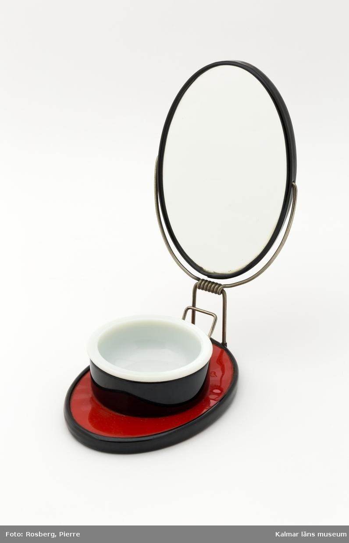 KLM 45058:62. Rakspegel med tvålkopp. Plast och metall. Ovalt reseetui i svart och röd plast. Spegel på lockets insida. Locket är fastsatt med kraftig metalltråd. Liten tvålkopp av vitt glas.