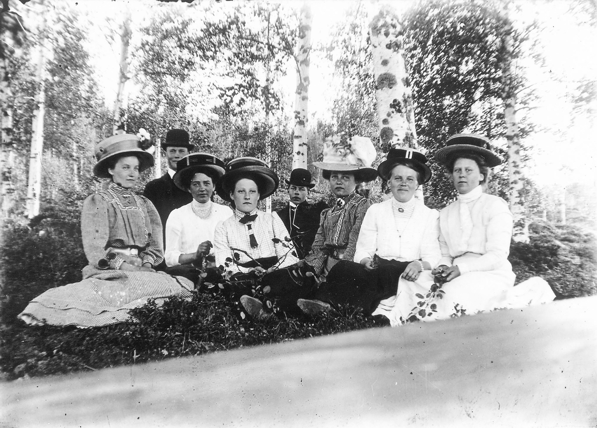 """Andra kvinnan från vänster är Stina Jonsson, Håbacken, född före 1890. Förlovad med """"Daniels-Jonas"""" i Hertsjö. Stina dog i spanska sjukan 1917-18. Hon hade 9 syskon, fem bröder och fyra systrar. Kvinnan längst till höger är eventuellt Marta (""""Lars-Pers""""). Per Herman Lindberg sitter i mitten."""