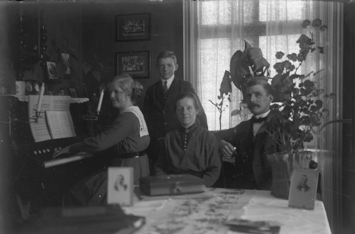 Familj, ung kvinna spelar orgel.