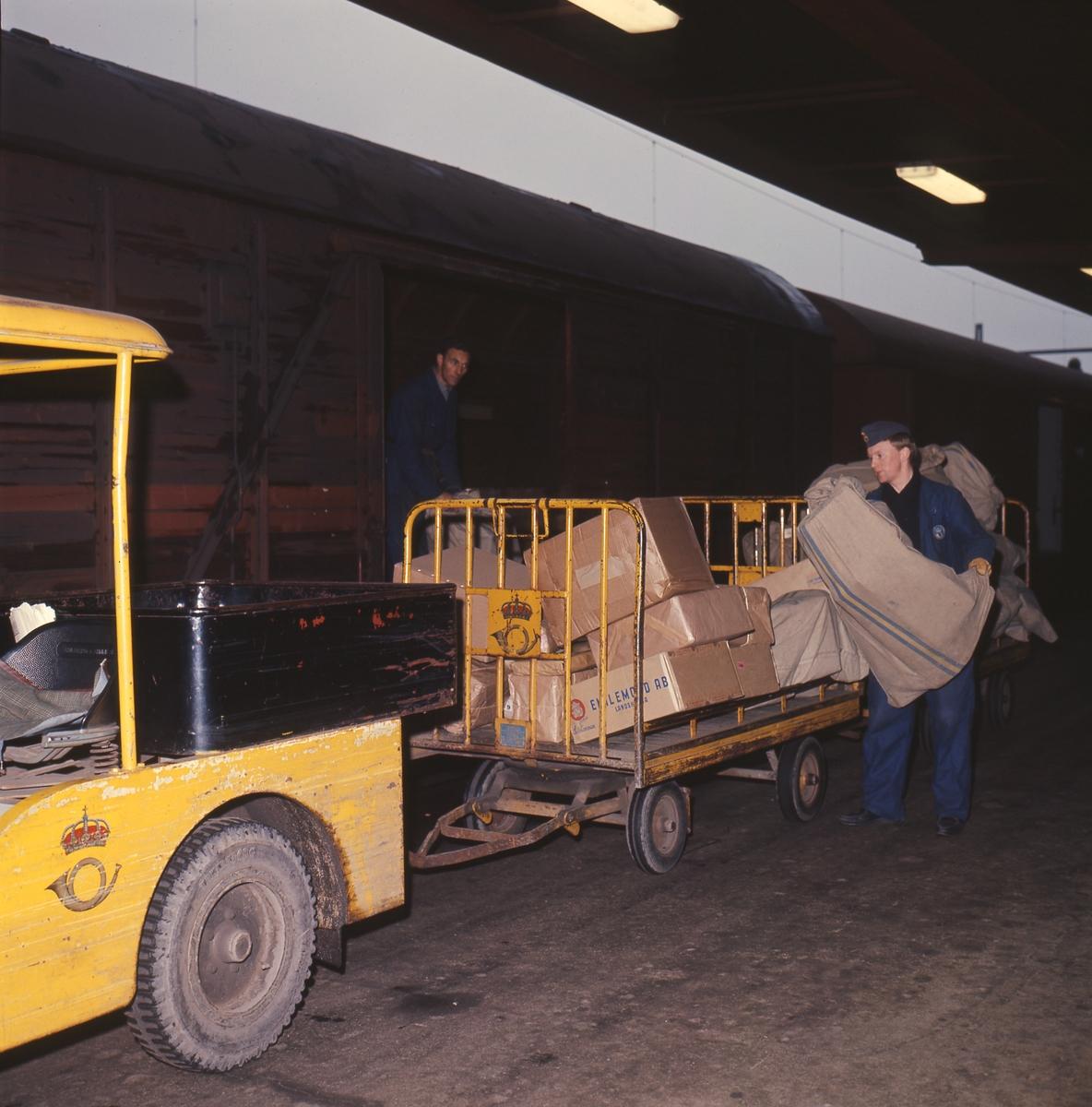 Lastning och lossning av post vid järnväg. Perrongtruck med släpvagn vid järnvägsvagn, 1960-talet.
