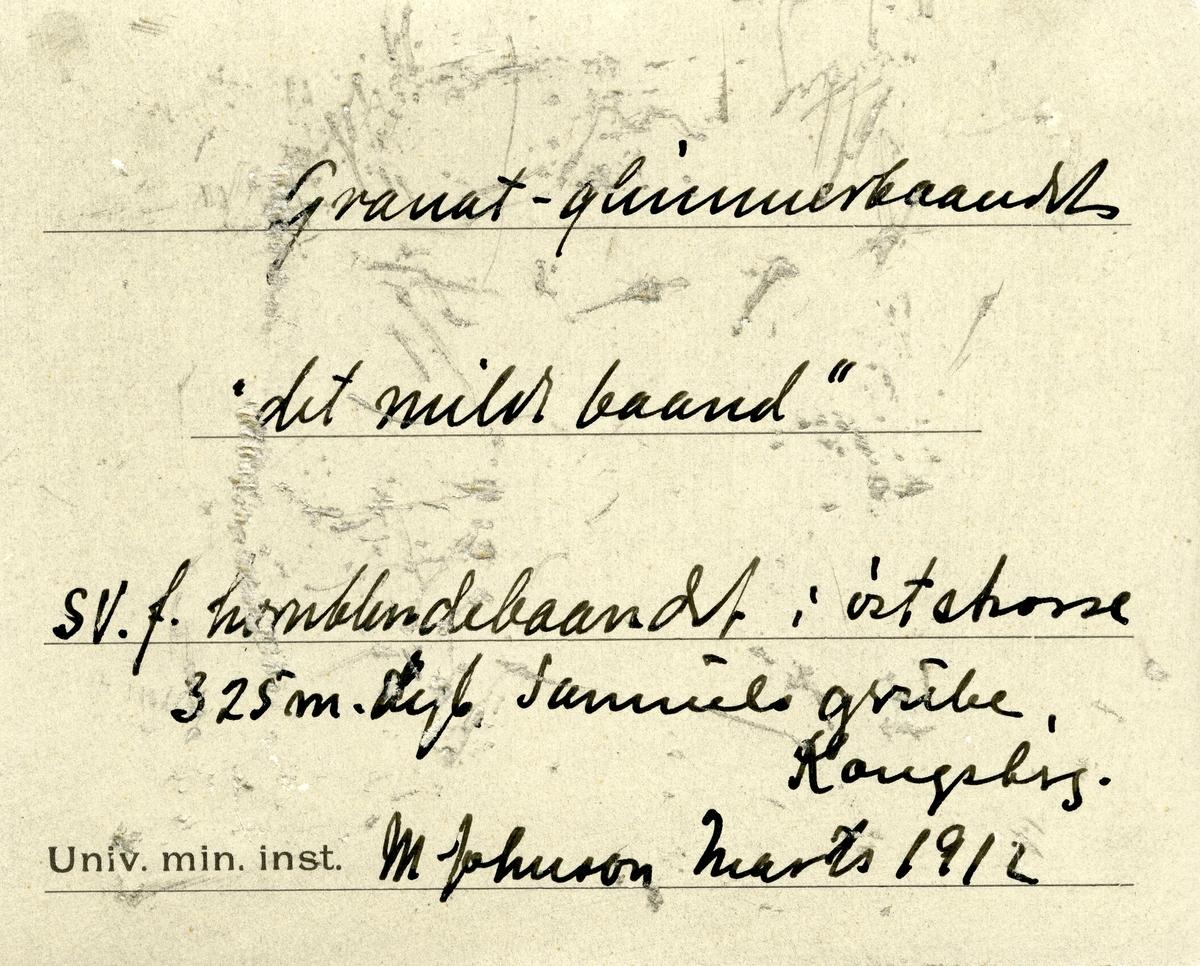 Etikett i eske: Granat-glimmerbaandet «det milde baand» SV. f. hornblendebaandet i øststrosse 325 m. dyb Samuels grube, Kongsberg. M. Johnson marts 1912  + papirlapp