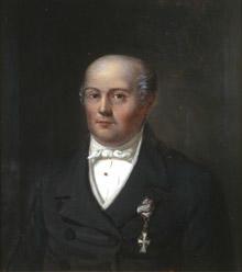 Portrett av Ole C Mørch. Mørk drakt, hvit skjorte, vest og halsbind. Orden festet på brystet.