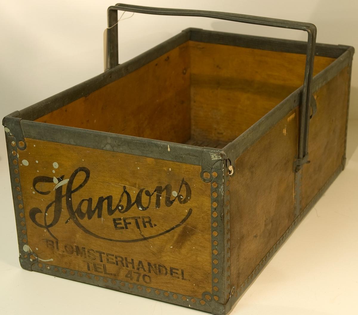 Transportlåda av board förstärkt med metall runt om i alla fogar. Metallhandtag. Märkt Hansons eftr BLOMSTERHANDEL TEL 470. på kortsidorna.