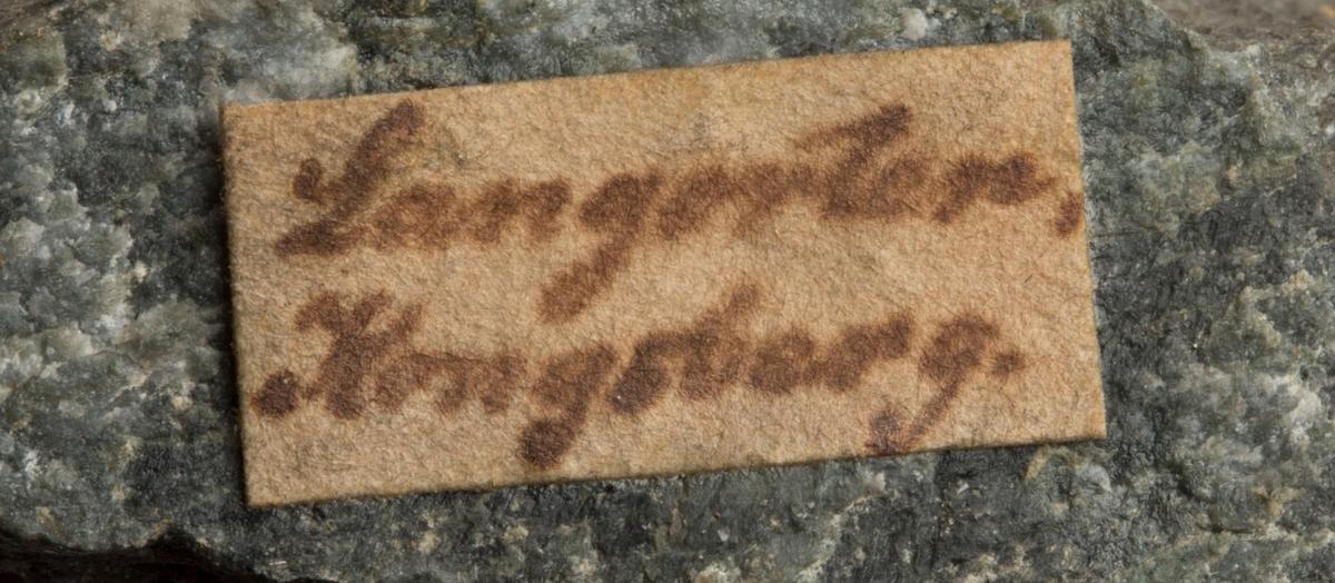 Etikett på prøve: Langorten. Kongsberg.  Etikett i eske: Ertsbaand med en Side- drum, fra Langorten, Kongsberg