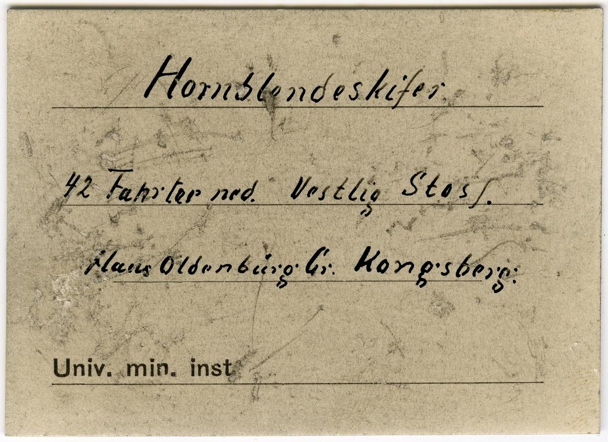 To etiketter i eske:  Etikett 1:  Indlagte er fra 42 Fahrter til Vest ved Nordgangen  Etikett 2: Hornblendeskifer 42 Fahrter ned. Vestlig Stoll. Haus Oldenburg Gr. Kongsberg.