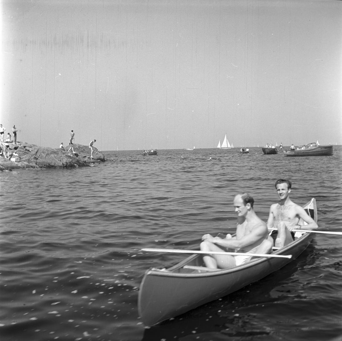Furuskär Furuviksparken invigdes pingstdagen 1936.  Två män i en kanot Badande människor på skäret