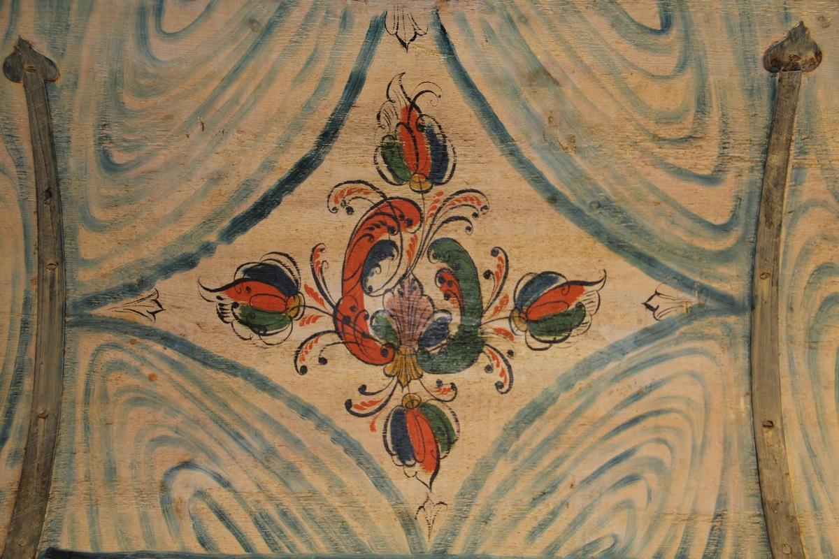 Kiste i tre med jernbeslag. Sink-konstruksjon. Rektangulær form. Svart bunn og flerfarga dekor, rosemalt. Ranker og blomsterknopper. Lokket innvendig malt av Peder Svadde.