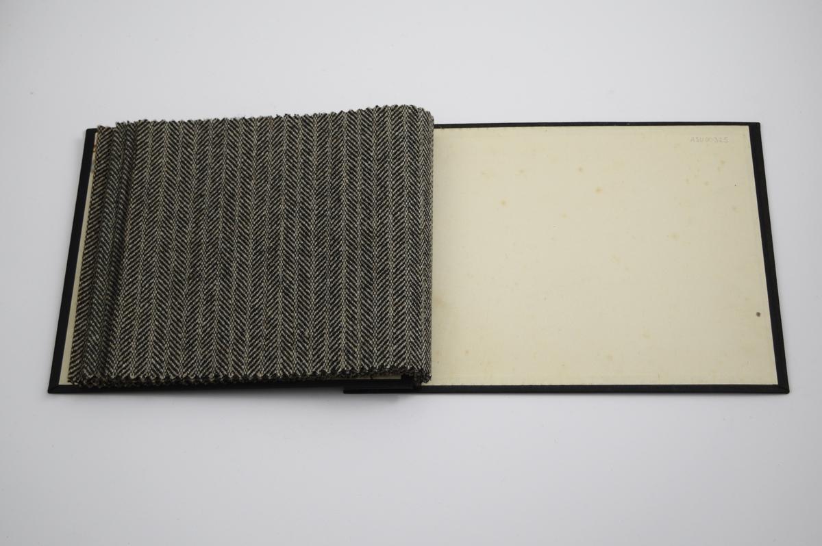 """Prøvebok med 4 prøver. Middels tykke stoff med fiskebensmønster og striper - mønsteret er tilnærmet likt på forsiden og baksiden av stoffet. Stoffene ligger brettet dobbelt i boken. Stoffene er merket med en rund papirlapp, festet til stoffet med metallstifter, hvor nummer er påført for hånd. Innskriften på innsiden av forsideomslaget viser at alle stoffene har kvaliteten """"Ola"""".   Stoff nr.: Ola/77, Ola/77B, Ola/78B, Ola/78."""