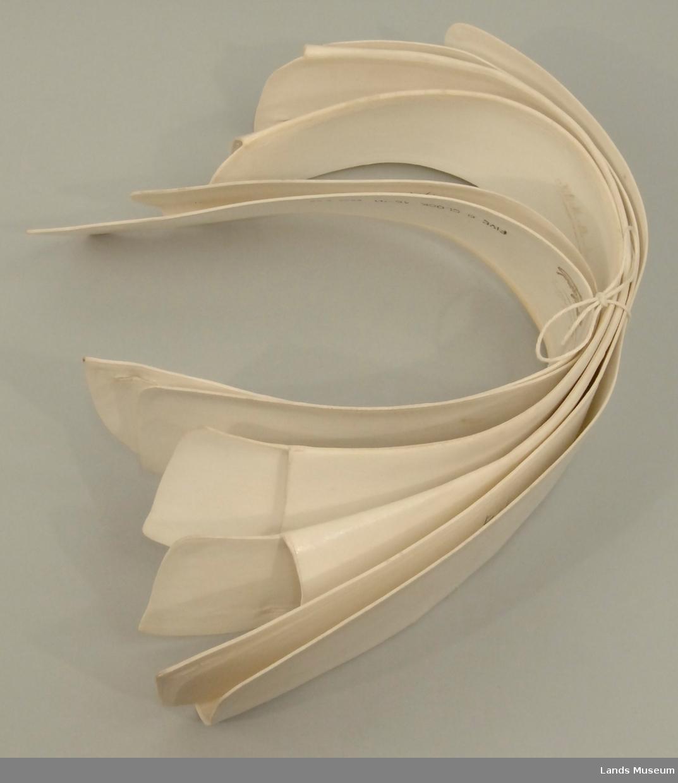 Løse snipper, hvite, stivede. Avrundede hjørner, litt plassert utenfor knepping i halsen. Bred form.