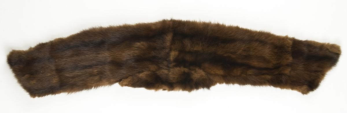 Avlangt pelsstykke, skreddersydd med pels på utsiden og fôrsilke. M/ekstra påsydd felt i nakken, dvs midt på.