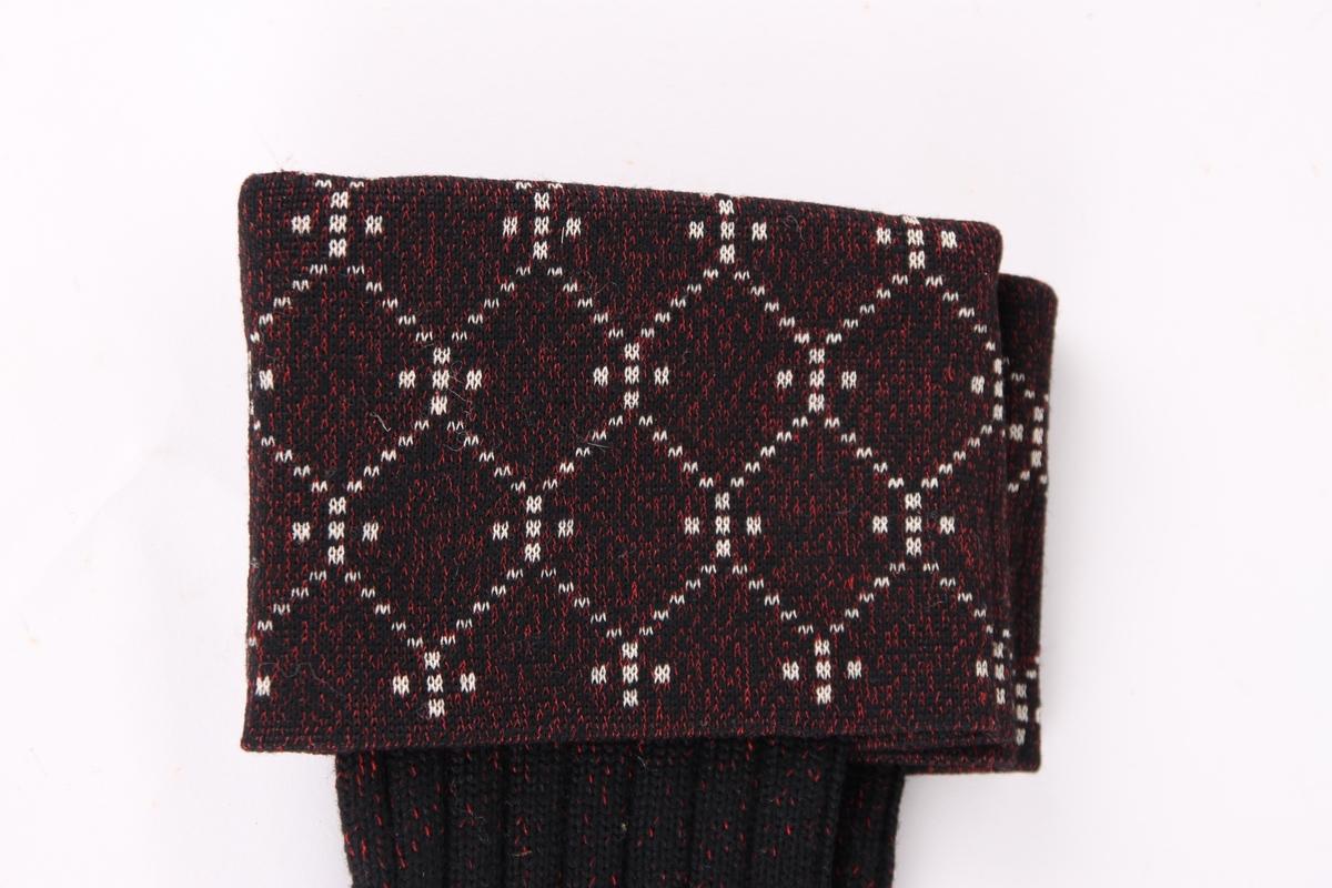Et par svarte sports-strømper med røde spetter. Strømpene har en 10 cm glattstrikket nedbrettskant med et hvitt mønster.