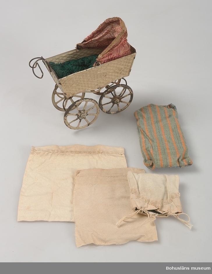 OBS endast sängkläderrna tillverkade av systrarna Bohlin.  Dockvagn av pressad plåt, beige. Suflett av rosa genomskinlig textil med röda blommor. Sängkläderna består av: 1 madrass i grönt, 1 st randig madrass i blått, grönt och orange, 1 st underlakan, 1 st överlakan samt kudde med örngott. Dockvagnen snarlik UM023810. Färgen avsliten på flera ställen.