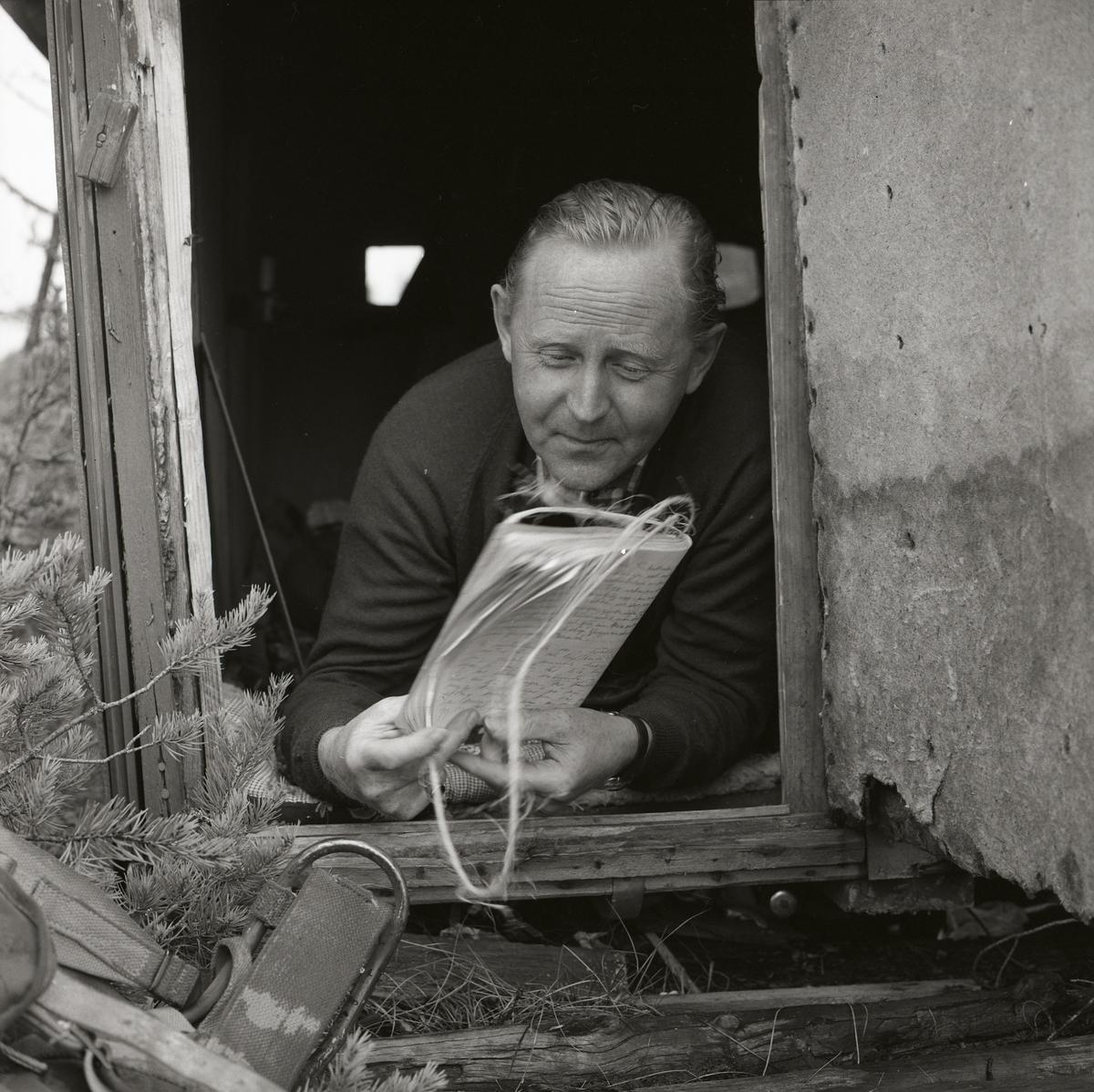 I en koja på Degelmyren ligger en man och läser i ett anteckningsblock. Kojans slitna dörr är öppen och mannen ligger lutad mot dörrkarmen. Längs ned till vänster skymtar axelband från en ryggsäck fram.