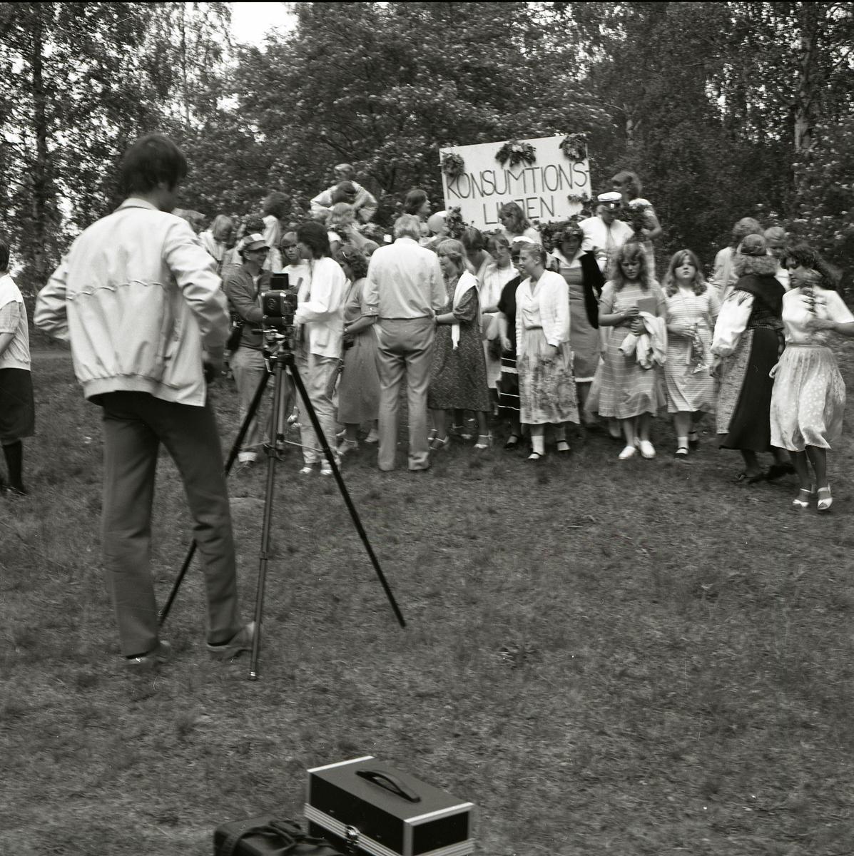 Konsumtionslinjen står skrivet på ett plakat dekorerat med blommor. Framför plakatet står en grupp med unga män och kvinnor i fina kläder och studentmössor. En fotograf står i förgrunden vid sitt stativ och har precis fotat gruppen som börjat skingra sig åt olika håll. Lövträden i bakgrunden bär sin fulla sommarskrud och skänker en sommarkänsla till bilden. Examensbilden är tagen i Bollnäs den 4 juni 1981.