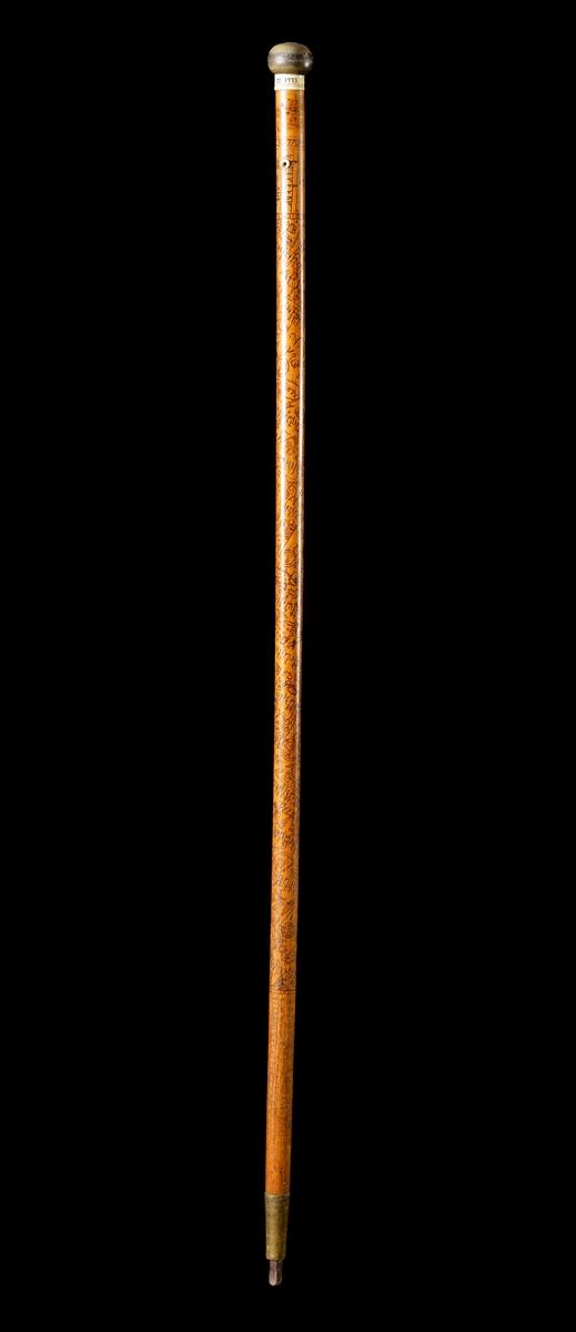Kalenderstav i form av en stavformad runkalender.  Staven är försedd med svarvad benknopp samt strax därunder en svarvad förstärkningsring av ben.  I spetsen på staven har den en doppsko, formad som en konisk mässingshylsa med en järndubb i änden. Runorna är inristade spiralformigt på staven. Signerad 1771.