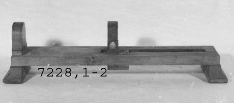 Skoblock av trä. Användes för mätning av storlek på sko. Tillverkades för beväringsförrådet vid Karlskrona örlogsstation år 1897. Blocket rektangulärt med fast uppstående klack i ena änden, på planet en inställbar löpare över två skalor med skonummer. Dessa är graderade 35-50 samt 18-40. Märkning: Beväringsförrådet vid Karlskrona Örlogsstation 1897 29/6.  Skalorna graderade 29-55 och 18-40 F.ö. = K 7228,1