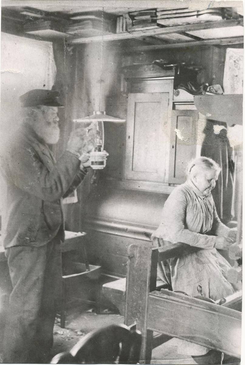 Andreas og Lisa Valstad. Hun vever, han tenner lampen. I kårstua.