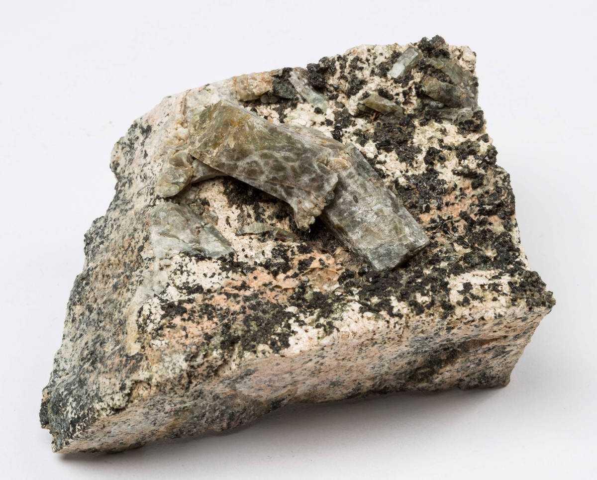 Apatitt, bøyd krystall, svakt grønnlig, på matriks, 3 sider skåret. Vegårshei?