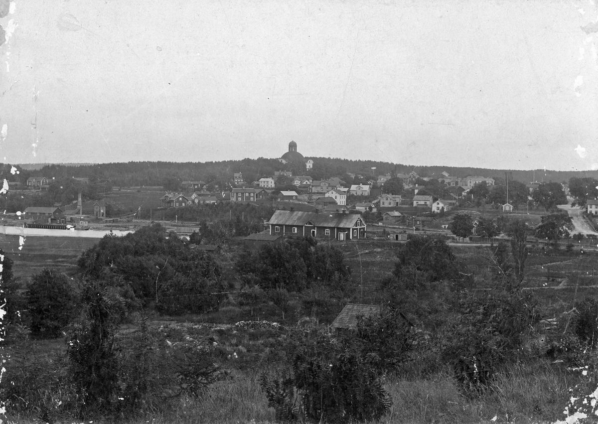 Vy över Kungsör. I bakgrunden Kungsörs kyrka med sin runda kupol. Till vänster ses Arbogaån som passerar Kungsör. Sent 1800-tal.