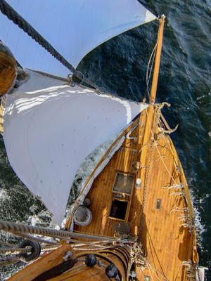 RS1 Colin Archer sett fra masta, utsikt over framdelen av dekket, to seil og litt av sjøen.