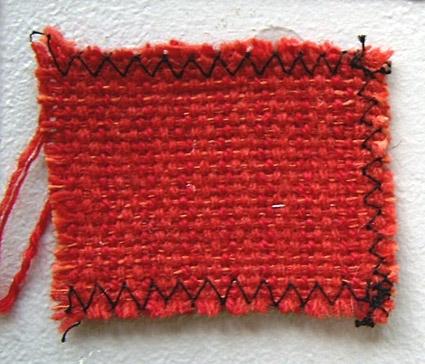 Vävprov, rödmelerat möbeltyg i ull och lin vävt i panamabindning. Varp i 1-trådigt och 2-trådigt ullgarn; möbeltygsgarn i olika nyanser rött. Två trådar löper tillsammans. Inslag i rött lingarn nr 16/1. Tre trådar tillsammans per inslag.