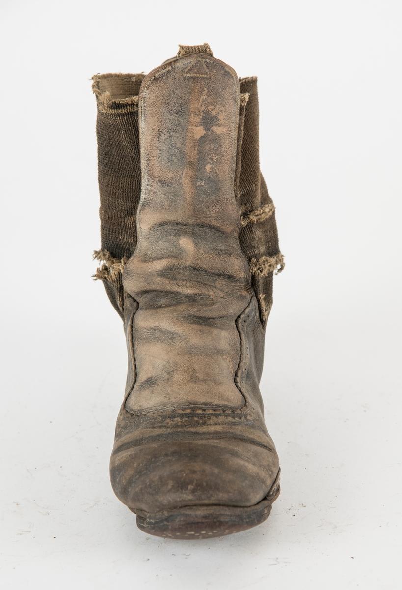 Støvel av skinn med eit stykke elastisk stoff i kvar side. Dekorert rundt ringinga. Pluggsko med låg hæl.
