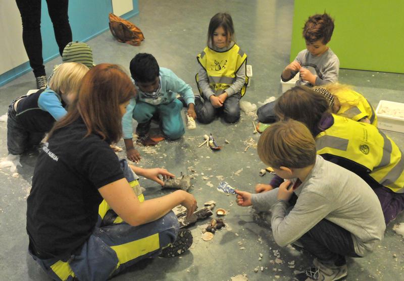 Barn sitter i sirkel, leker arkeologer, graver ut funn fra sandkasser. (Foto/Photo)