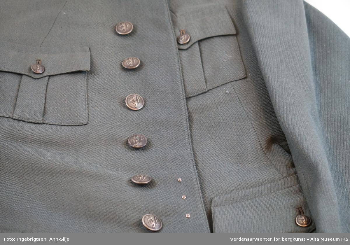 Uniformsjakke: Enkeltspent uniformsjakke med to brystlommer og to vanlige lommer. Lommene lukkes med knapper. Kragen er kantet fra skulder og ned til halsen med sølvfarget bånd, og det er festet 2 stjerner på hver side av kragen. På fremsiden av venstre skulder er det dekoreringer i fargene rød, gul, lilla, hvit og mørkerød. Knappene har relieff med Norges riksvåpen. Jakken har splitt bak. Nederst på hvert erme er det en grønn pyntekant som går opp i en spiss.   Sabelen: Forgyllt messingfeste med støpt og gravert nakkestykke. Trekavel trukket med rokkeskinn med messingtrådvikling i rillene.  Nedbøyd bakre parérstang. Gjennombrutt parérplate med drageornamentikk med riksløven av 1906. Rett kileformet klinge med blodrand og ryggslipning mot spissen. Stålbalg med bærehempe.