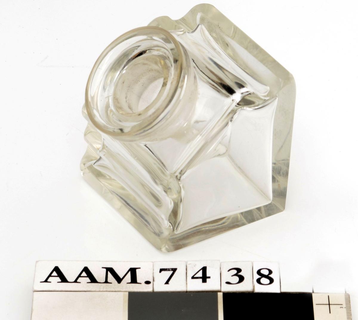 """Blekkhus av tykt glass, med firkantet bunn med tekst:  """"Reg. No. 19621.""""  oversiden har to filtdypninger for  penneskaft, nederst på forsiden en tilsvarende  fordypning, men uten funksjon. Skrå forside med  sirkulær munningsbrem, i denne passer liten trakt-  form med smal åpning i bunnen."""