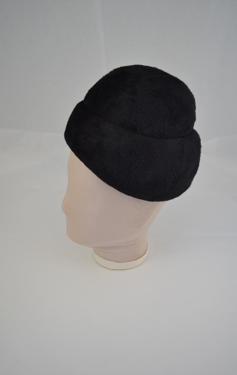 Svart børstet filt. Rund pull, dype lagte folder utgjør hattens fasong. Svart silkefor.