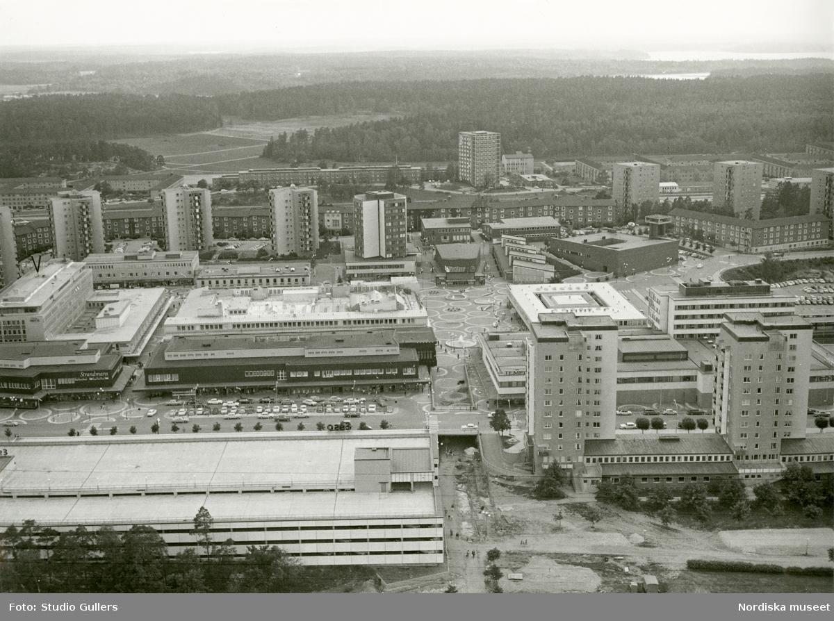Flygbild över Vällingby centrum med skogslandskap i bakgrunden.