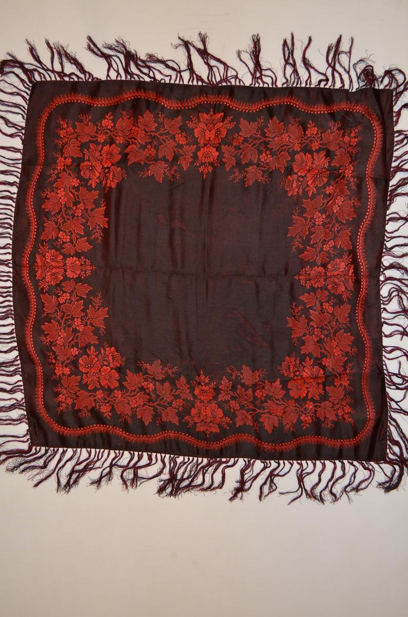 Tørkle i svart silkedamask med rosafiolette rosebordar langst kantane. Påsette frynser i svart og rosafiolett, 10,5 cm lange.