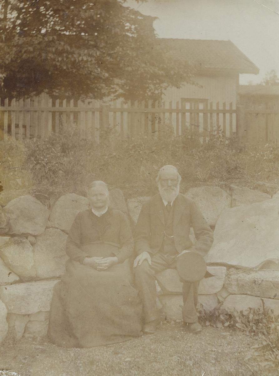 Lisa og Andreas Olsen Valstad sitter på stenbenk, hus og stakittgjerde i bakgrunnen.