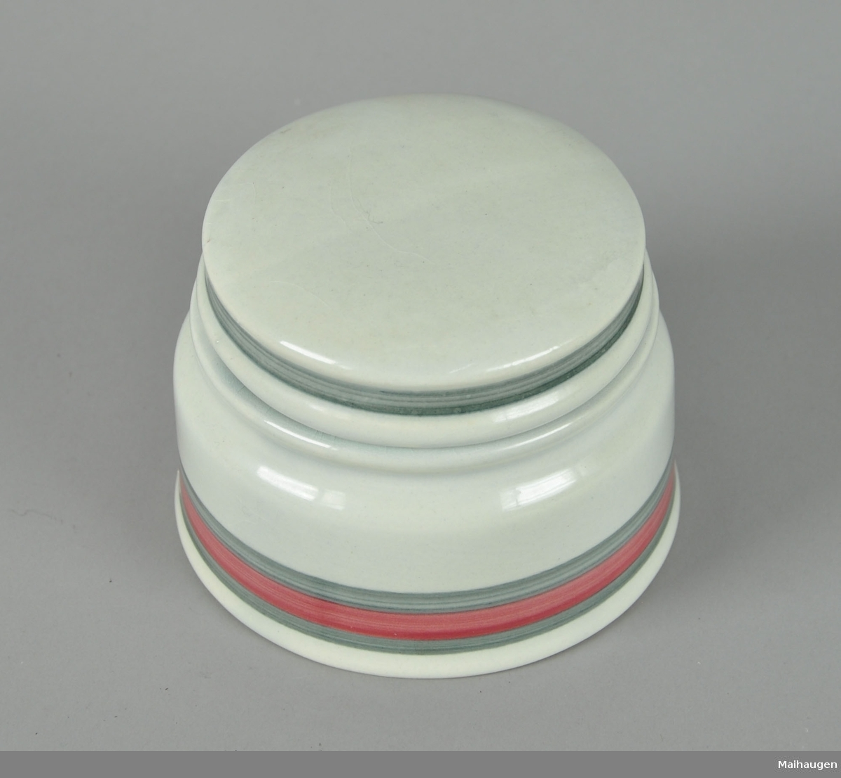 Skål med lokk, av glassert keramikk. Har påmalte striper på lokk og korpus i grå og røde farger. Har eldre sukkerpakker på innsiden.