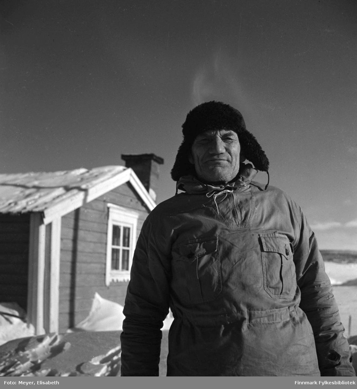 Isaac Johansen Hætta fotografert i solskinnet utenfor en av Statens fjellhytter, muligens Gargia Fjellhytte. Han har på seg fjellanorakk og skinnlue på hodet.  Fotografert av Elisabeth Meyer, muligens påsketider 1940.