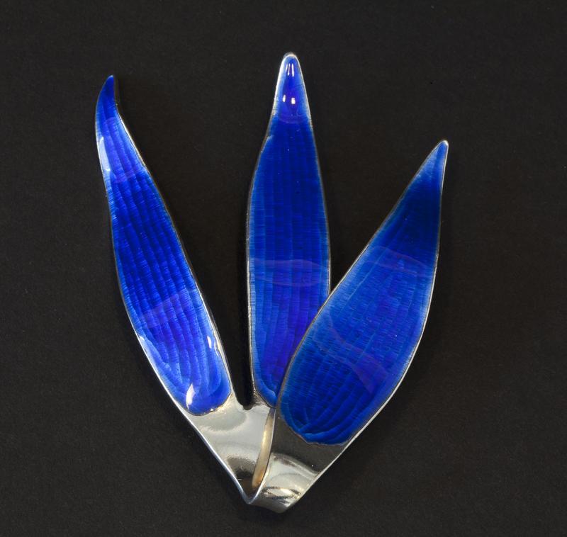 Brosje i sølv med blå speilemalje. Utformet som et tre blader