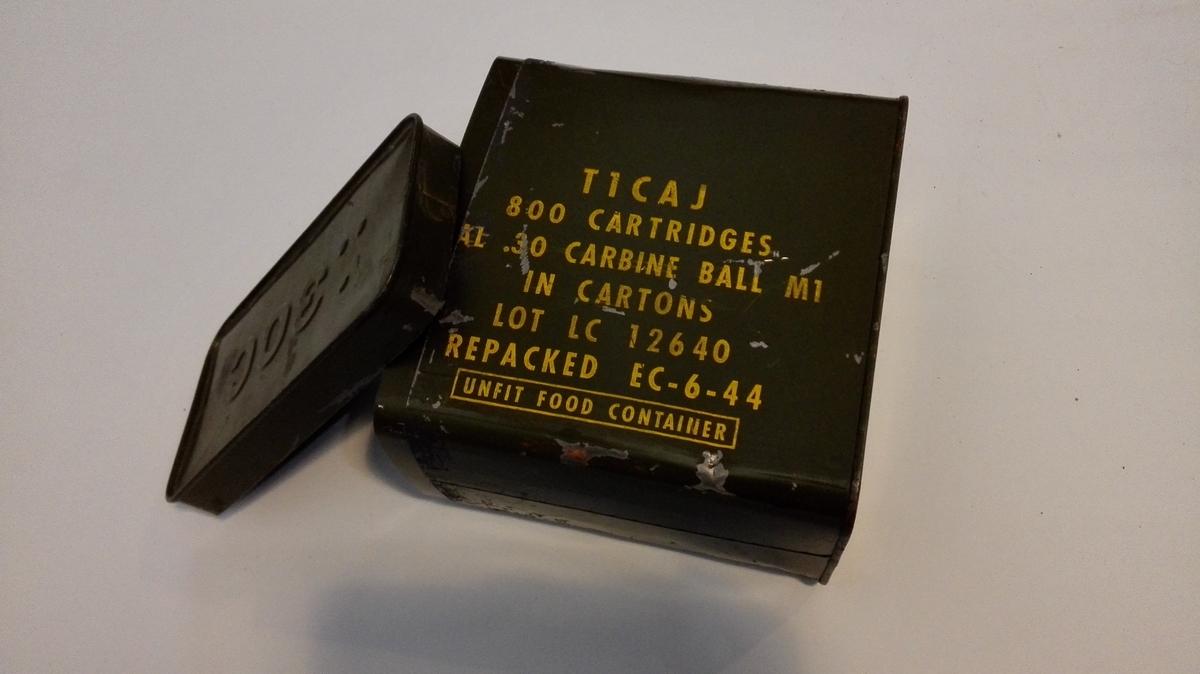 Militærgøn metallboks med laust lokk og eit handtak. Innsidaerkleddmed pappkartong. På loket er utstansa tre prikkaar, som ein trekant, og 30C. Har vore brukt til å oppbevara ammunisjon til US Carbin .30 gevær.