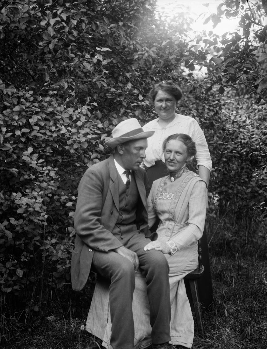 Karin Arnell med Gunnar och Anna Johansson i trädgården i Sävasta, Altuna socken, Uppland