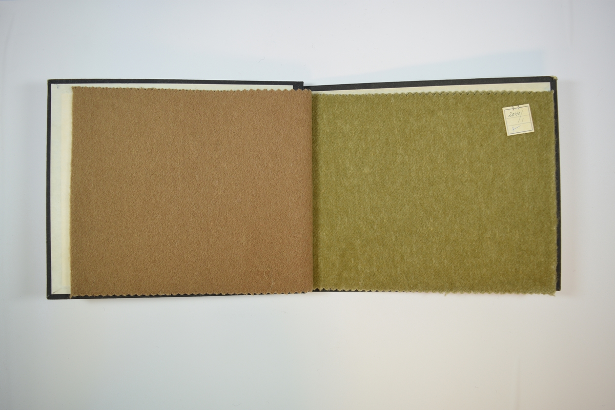 Rektangulær prøvebok med to stoffprøver og harde permer. Permene er laget av hard kartong og er trukket med sort tynn tekstil. Boken inneholder relativt tykke stoff, det ene ensfarget det andre melert. Stoffenes rettside er har et tovet/valket utseende, mens baksiden har tydeligere vevmønster. Stoffene er merket med en firkantet papirlapp, festet til stoffet med metallstifter, hvor nummer er påført for hånd. Begge lappene har et kryss i nederste venstre hjørne laget med blå kulepenn.  Stoff nr.: 2040/2, 2040/1.
