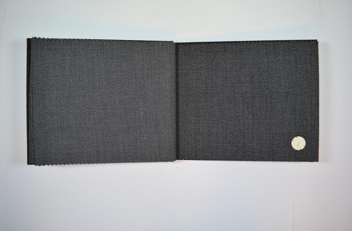 Rektangulær prøvebok med fire stoffprøver og harde permer. Permene er laget av hard kartong og er trukket med sort tynn tekstil. Boken inneholder relativt tynne melerte stoff. Toskaftbinding. Alle stoffene ligger brettet dobbelt i boken slik at vranga dekkes. Stoffene er merket med en rund papirlapp, festet til stoffet med metallstifter, hvor navn eller nummer er påført for hånd. Innskriften på innsiden av forsideomslaget indikerer at alle stoffene i boken har kvalitetsnummer 2850.  Stoff nr.: 2850/1, 2850/2, 2850/3, 2850/4.