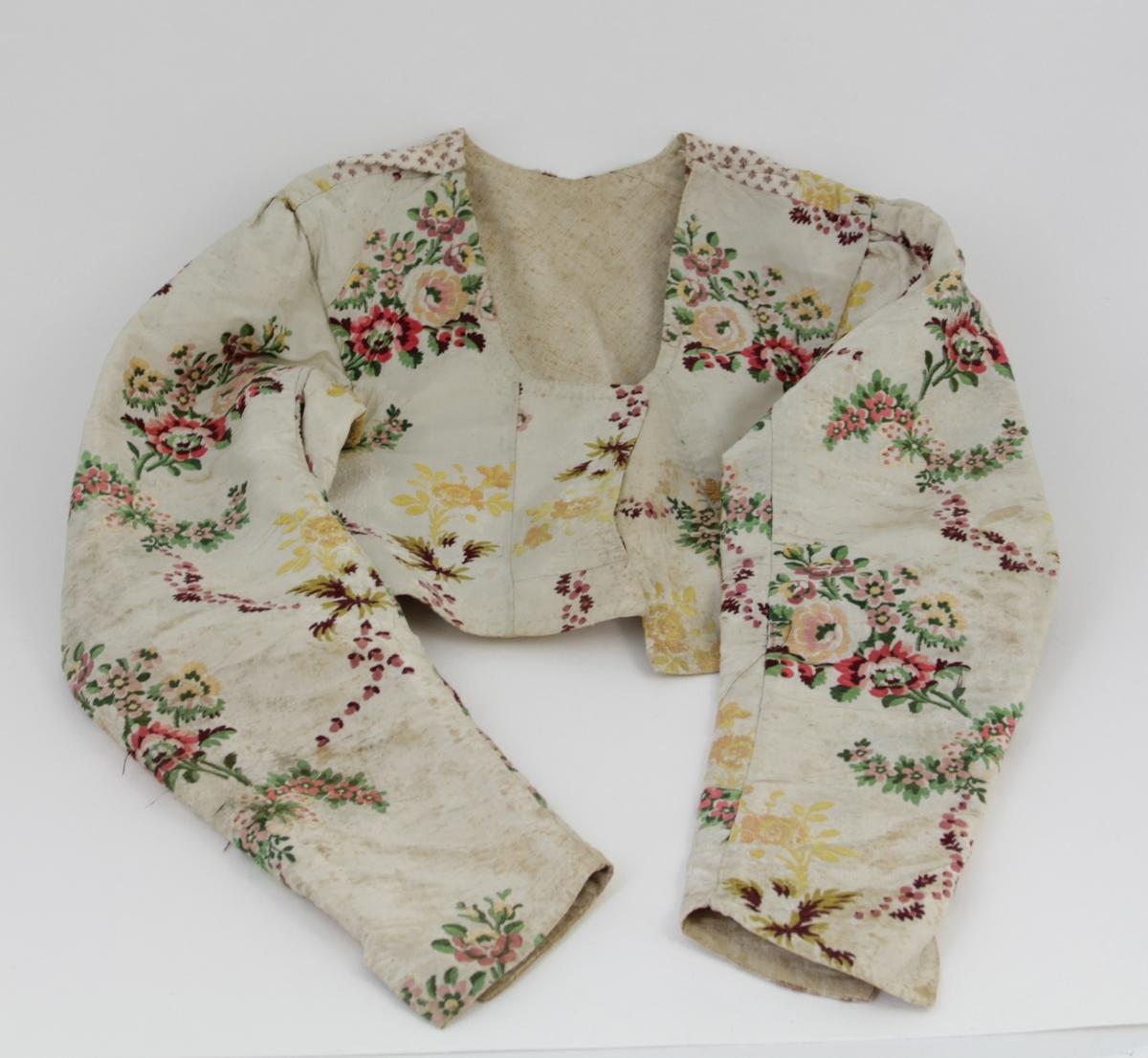 """Deler av den såkalte Mosbybunaden eller Torridalsdrakta. Liv, trøye og sjal. Det er usikkert om de tre delene hører komplett sammen, eller om de har blitt brukt til forskjellige tider.  a) trøye eller jakke i brosjert silke. blomstermønster i gult, rosa, brunt og grønt. Foret med linlerret, skjøtet med bomullsstoff under armene og ved skuldersømmer. Dette stoffet er hvitt med små blomster. Rund hals. Ingen spor etter hekter eller annen lukkemekanisme foran. Ermene er ledd rynket på toppen. Splitt i bunnen av ermene. Hele trøyen er håndsydd. Nyere håndsting i halsen for å sy inn, akkurat denne delen av sømmen er grovt arbeide.   b) liv eller vest i rutet stivt bomullsstoff, med rød som hovedfarge. Sydd sammen av fire deler, to bakstykker og to forstykker. Innsydd i forstykket på begge sider i senere tid. Sydd i kantene med både håndsting og maskinsting. Uklart hvilken søm som er den primære. Foret med ubleket bomullstoff. Lukkes med fire hekter foran, men kun 1 gjenstår. Trekantet kile nederst bak. Kalt """"opplut"""" i registrering fra Torridal historielag. c) sjal eller tørkle i ullmusselin, 6 tråder """"tafs"""" 6x8 cm. I en lys grågul farge, med blomstermønster ordnet i geometriske seksjoner, i blått, grønt og to nyanser av rosa/dyprød."""