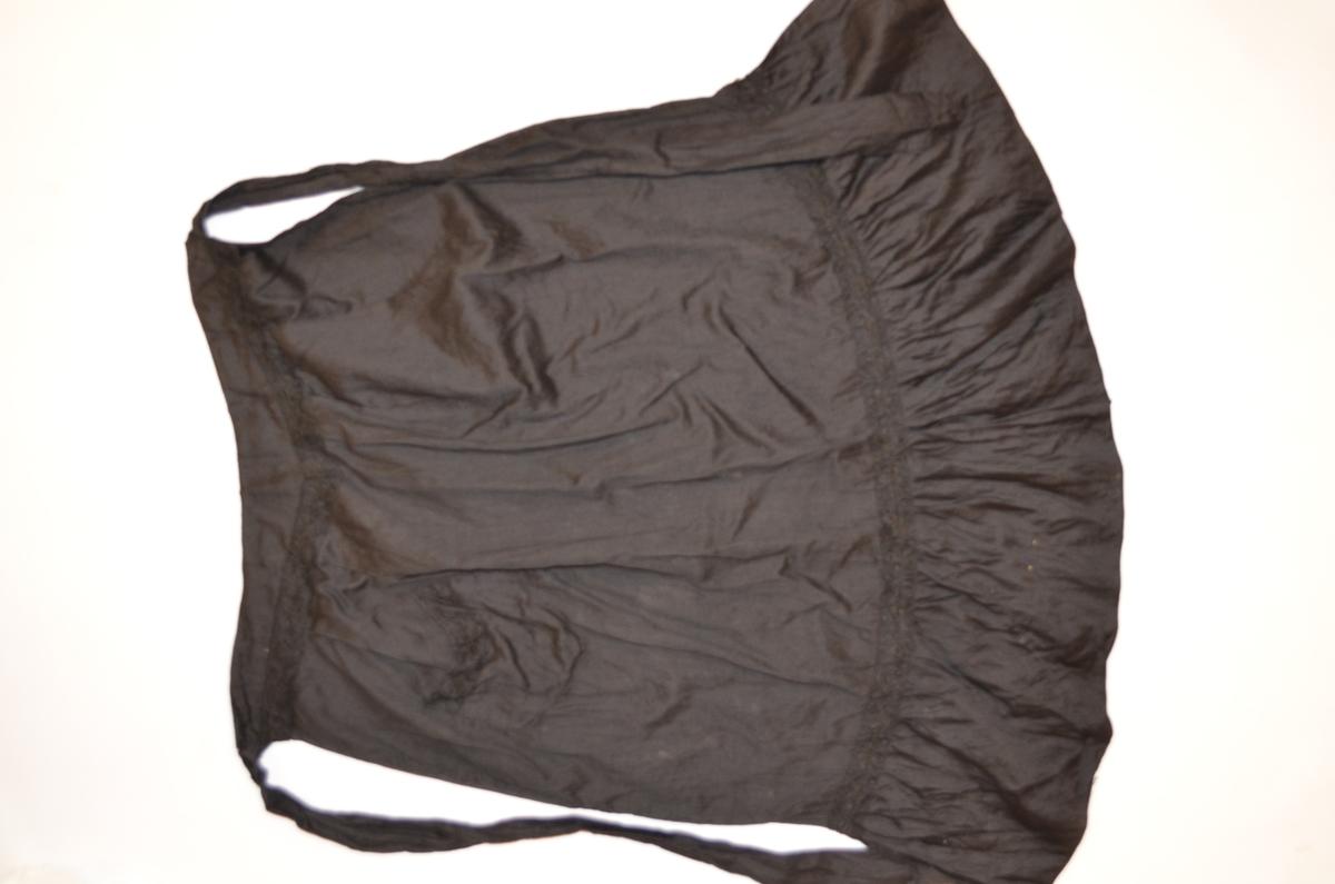 Forkle i svart bomull med motfold midt framme og to folder på kvar side, linninga går ned i ein liten spiss. Kappe nederst med små folder. Lita lomme. Påsydd svart blonde øvers, nede på forkledet og på lomma.