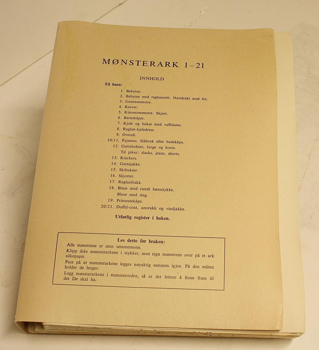 """Rektangulær, stående koffert. Lokk, håndtak og lås. Innhold: """"Den Store Norske Syboken"""" Dovre Mønster. Forfatter: Ella Lund. To holdere med mønsterark (1-21 og 22-42)."""