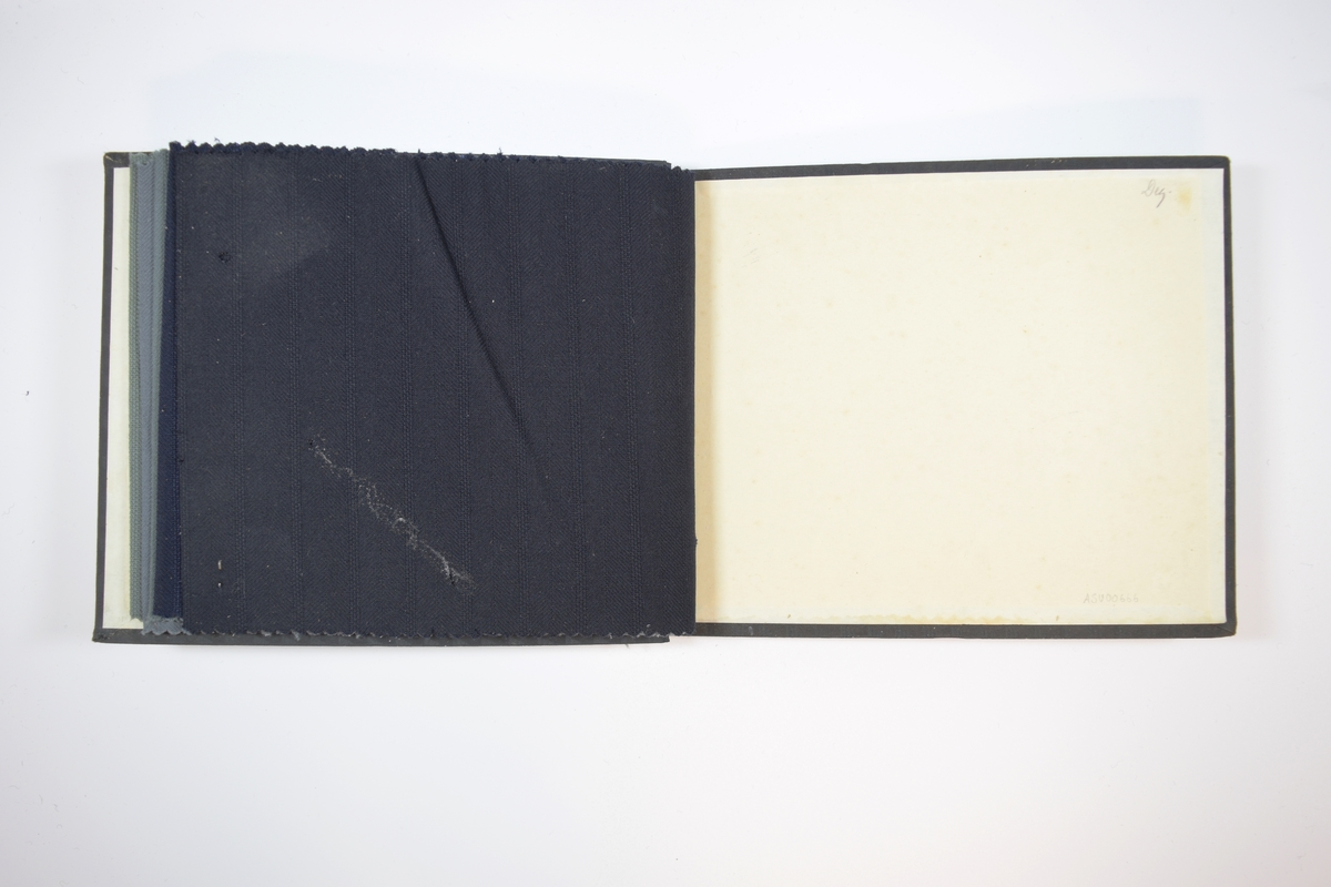 """Rektangulær prøvebok med harde permer og seks stoffprøver. Permene er laget av hard kartong og er trukket med sort tynn tekstil. Boken inneholder middels tykke ensfargede stoff med fiskebensmønster og striper. Kyperbinding/diagonalvevd m.m. Stoffene ligger brettet dobbelt i boken slik at vranga skjules, men mønsteret er det samme på baksiden. Stoffene er merket med en pæreformet papirlapp, hvor overflaten er imitert til å ligne treverk, festet til stoffet med metallstifter, med nummer påført for hånd. På baksiden av lappen står det skrevet """"NORSK FABRIKAT"""" i nasjonale farger.   Stoff nr.: 6000/1, 6000/2, 6000/3, 6000/4, 6000/5, 6000/6."""