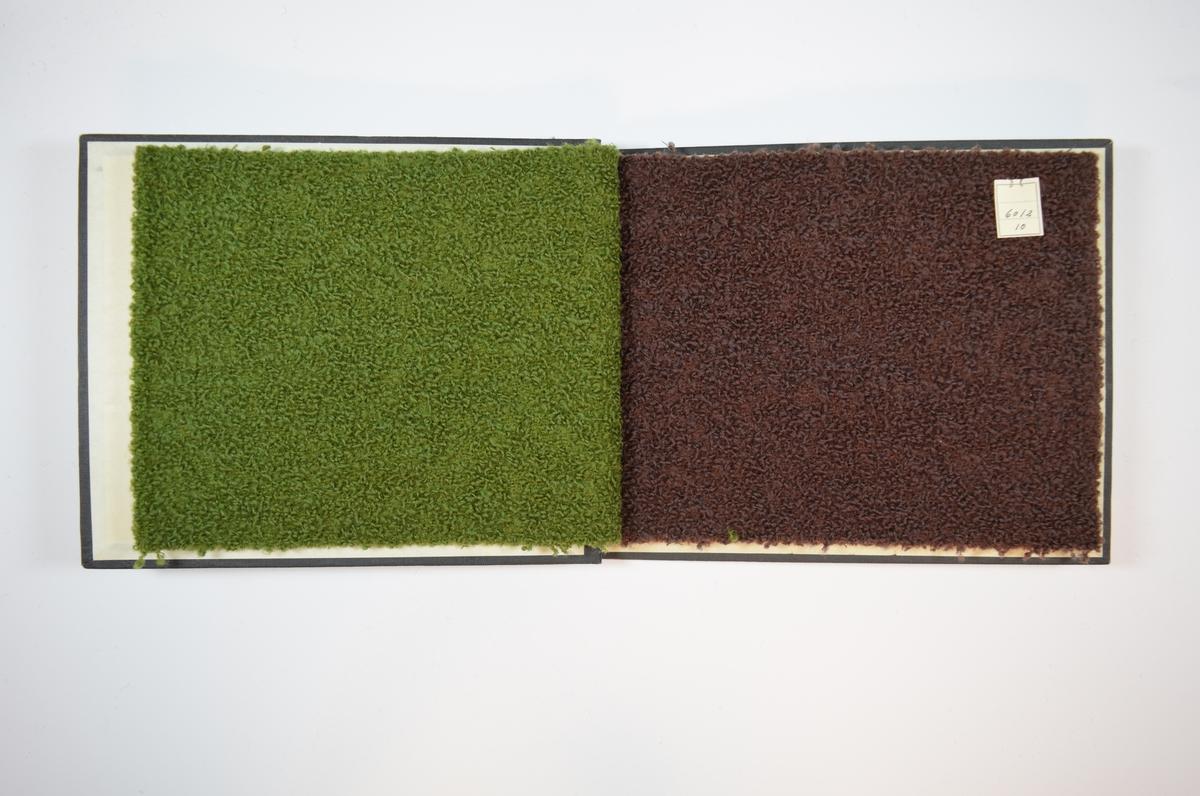 Rektangulær prøvebok med harde permer og tre stoffprøver. Permene er laget av hard kartong og er trukket med sort tynn tekstil. Boken inneholder tykke ensfargede stoff. Baksiden av stoffet er laget av relativt tynne tråder i toskaftbinding, hvor en svært tykk tråd er vevd inn på forsiden. Stoffets forside fremstår som buklete/knudrete. Stoffene er merket med en firkantet papirlapp, festet til stoffet med metallstifter, hvor nummer er påført for hånd.  Stoff nr.: 6012/9, 6012/10, 6012/11.