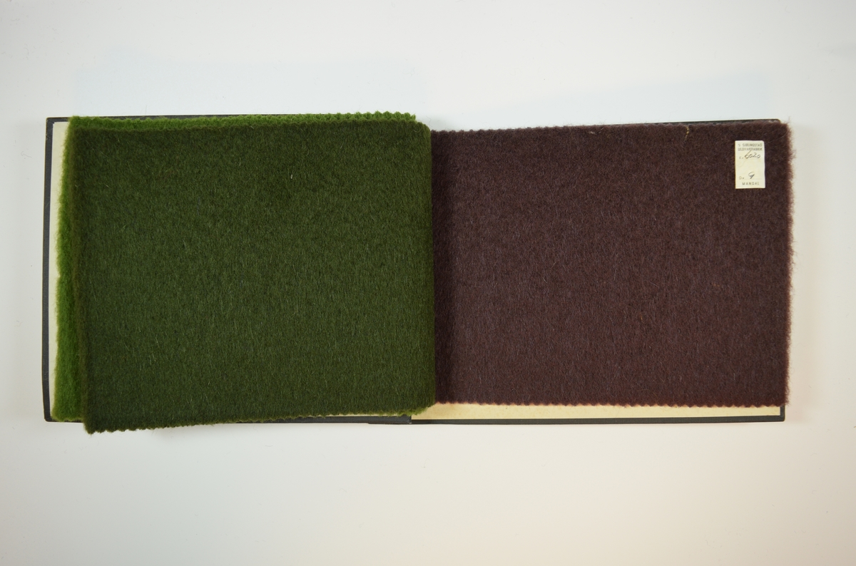 Rektangulær prøvebok med harde permer og tre stoffprøver. Permene er laget av hard kartong og er trukket med sort tynn tekstil. Boken inneholder tykke ensfargede ullstoff. Stoffene ligger brettet dobbelt i boken slik at vranga skjules. Stoffene er merket med en firkantet papirlapp, limt til stoffet, hvor nummer er påført for hånd. En lapp på innsiden av omslagets bakside gir informasjon om stoffene.   Stoff nr. 6020/7, 6020/8, 6020/9.