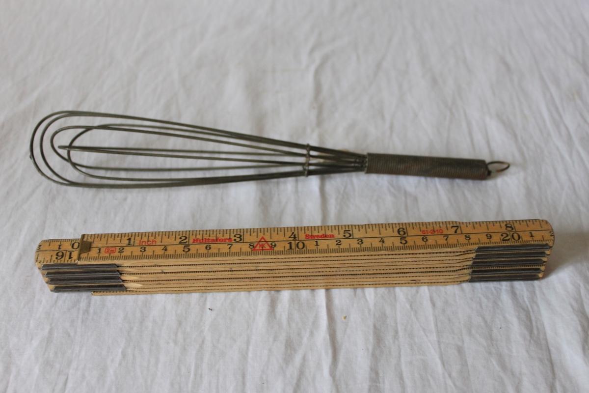 Luffararbete. Visp av järntråd som är böjd till en oval ögla med spiralvriden tråd. Rakt virat skaft avslutat med trädarna tillbakaböjda 10-12 cm