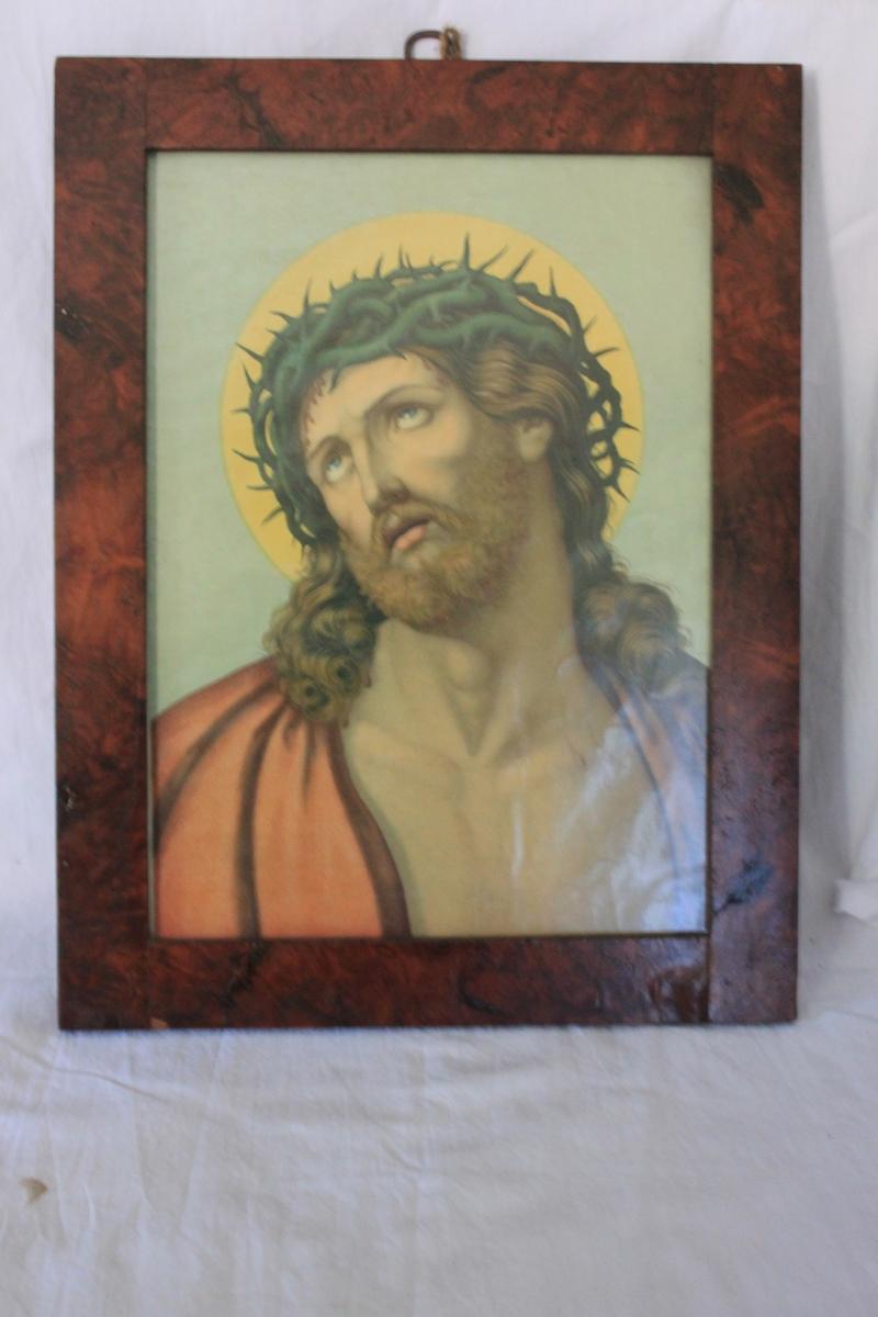 Oljetryck i färg föreställande Kristus med törnekrona. Slät ram av mahognyfanerad furu, glasad.